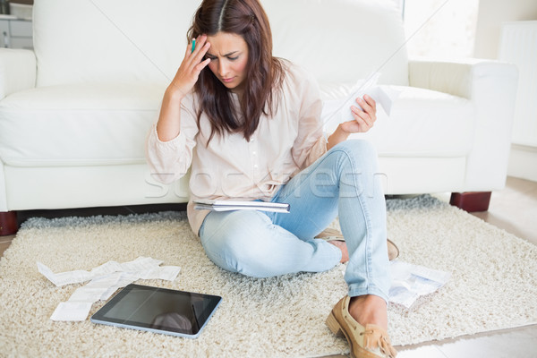 Woman with tablet pc calculating bills on the carpet Stock photo © wavebreak_media