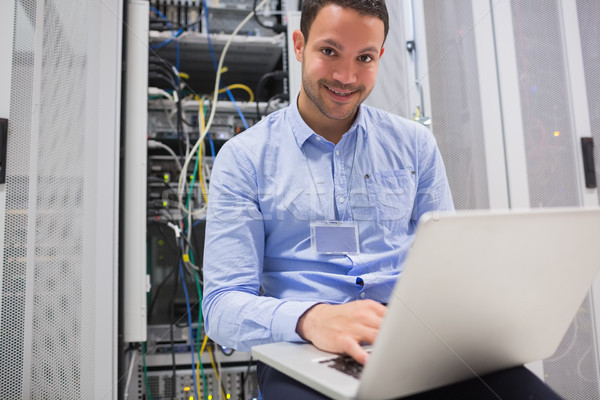 Happy man using laptop to check servers in data center Stock photo © wavebreak_media