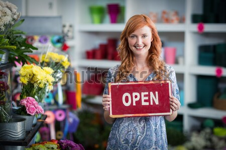 Woman in garden center pointing at the open-sign while smiling Stock photo © wavebreak_media