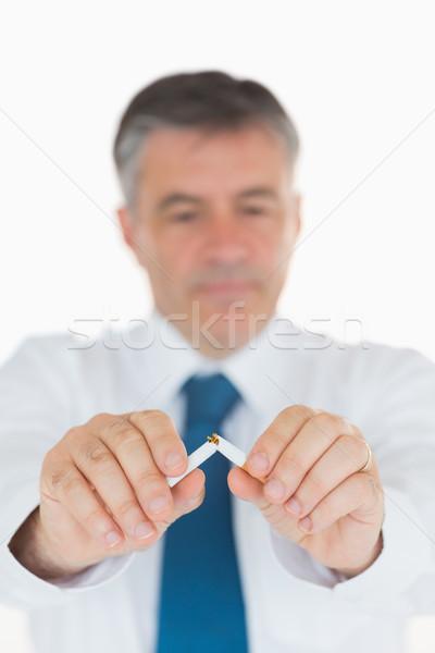 Man concentrating on breaking cigarette in half  Stock photo © wavebreak_media