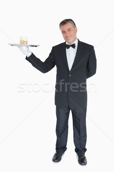 Smiling waiter holding silver tray with glasses of whiskey Stock photo © wavebreak_media