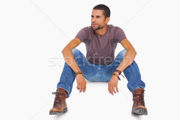 Handsome man sitting on floor and looking away Stock photo © wavebreak_media