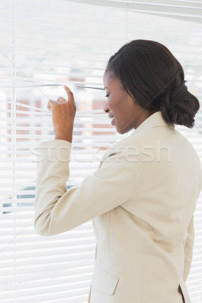 Businesswoman peeking through blinds in office Stock photo © wavebreak_media