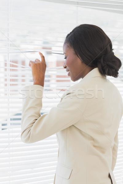 Stock photo: Businesswoman peeking through blinds in office
