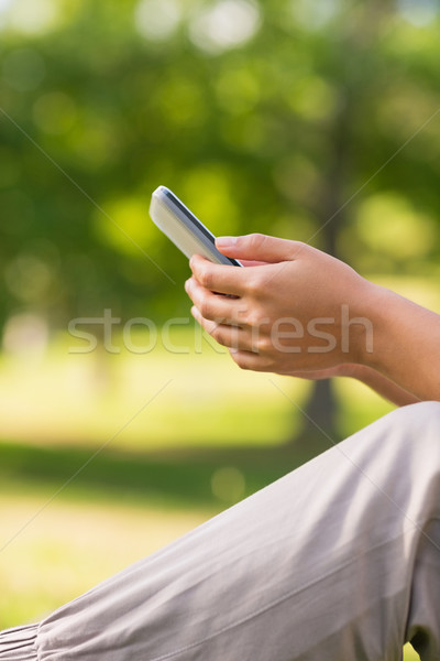Mid section of a woman text messaging in park Stock photo © wavebreak_media