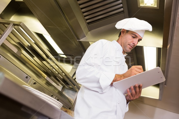 Concentrated male cook writing on clipboard in kitchen Stock photo © wavebreak_media