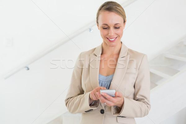 Smiling estate agent sending a text message Stock photo © wavebreak_media