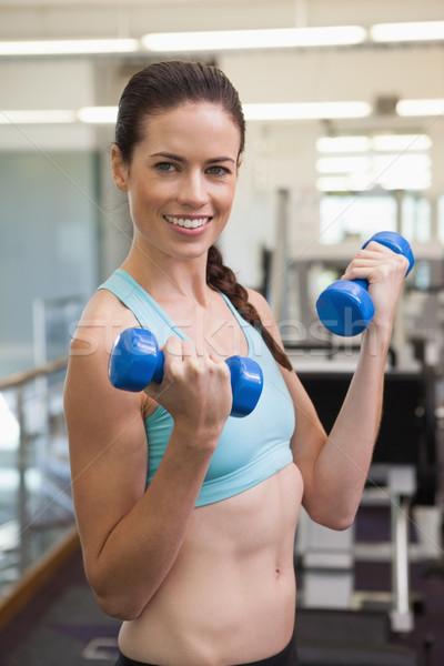 Fit smiling brunette lifting blue dumbbells Stock photo © wavebreak_media