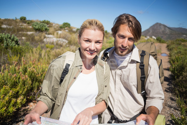 Hiking couple walking on mountain terrain holding map smiling at Stock photo © wavebreak_media