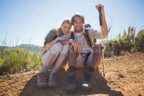 Hiking couple taking a break on mountain terrain smiling at came Stock photo © wavebreak_media