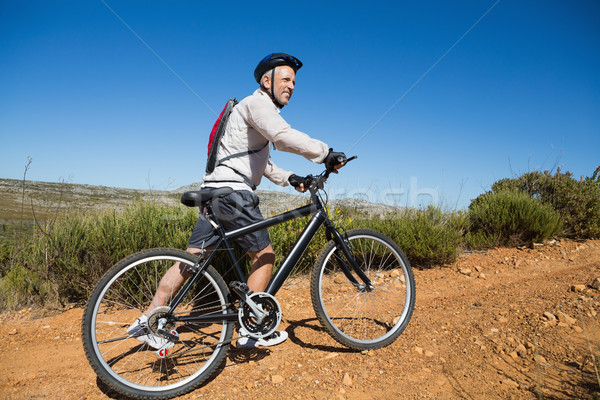 Fit cyclist pushing bike uphill on country terrain Stock photo © wavebreak_media