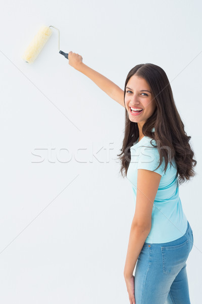 Happy young brunette painting with roller Stock photo © wavebreak_media