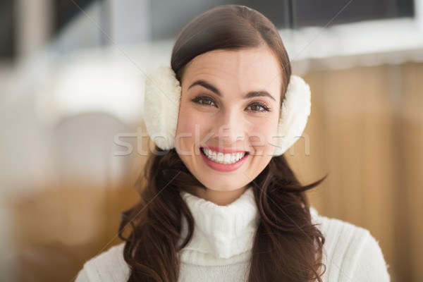 Beauty brunette with ear muffs smiling at camera Stock photo © wavebreak_media