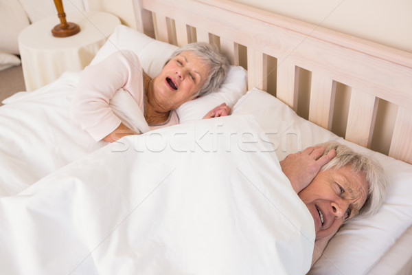 Senior man blocking out his wifes snoring Stock photo © wavebreak_media
