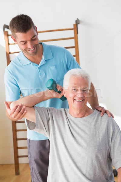 Stock photo: Senior man training with his coach