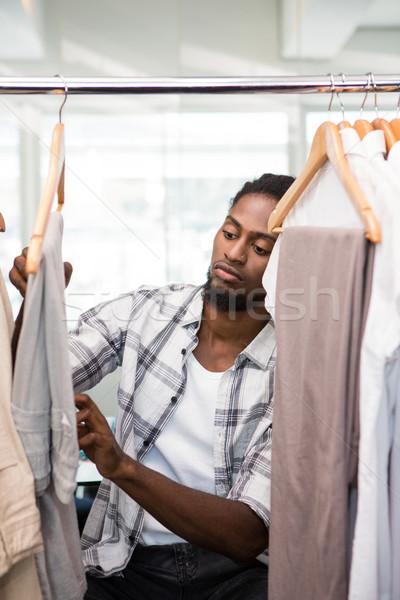 Maschio moda designer guardando rack vestiti Foto d'archivio © wavebreak_media