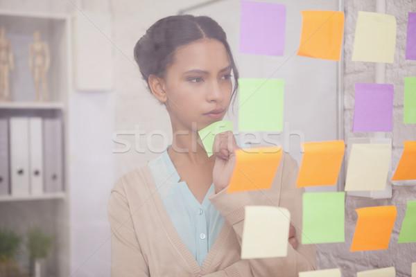Zamyślony kobieta interesu patrząc karteczki okno biuro Zdjęcia stock © wavebreak_media