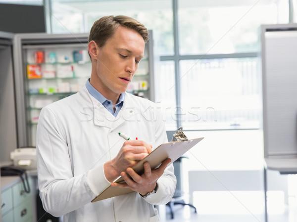 Bello farmacista iscritto appunti ospedale farmacia Foto d'archivio © wavebreak_media