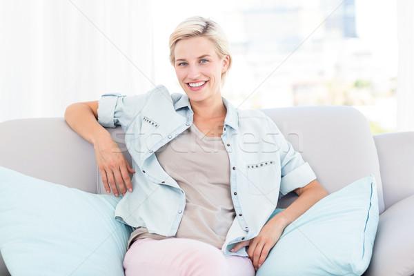 Ziemlich blonde Frau Sitzung Couch lächelnd Kamera Stock foto © wavebreak_media