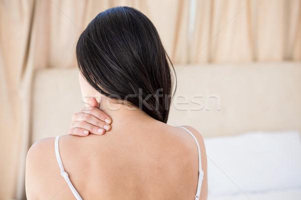 Bastante morena dolor de cuello cama casa mujer Foto stock © wavebreak_media