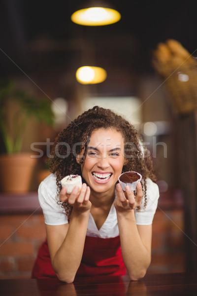 Nevet pincérnő mutat kettő minitorták portré Stock fotó © wavebreak_media