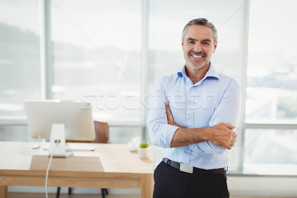 Portrait of smiling executive standing with arms crossed Stock photo © wavebreak_media