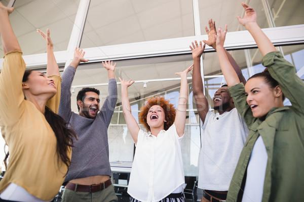 Derűs kollégák karok a magasban áll iroda üzletember Stock fotó © wavebreak_media