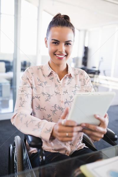 Portrait of smiling businesswoman using digital tablet while sitting on wheelchair Stock photo © wavebreak_media