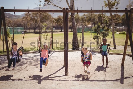 Stock photo: Trainer guiding schoolkids on swing
