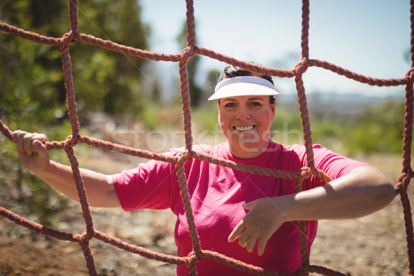 Portrait of happy woman standing near net during obstacle course Stock photo © wavebreak_media