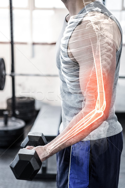 Highlighted arm of strong man lifting weights at gym Stock photo © wavebreak_media