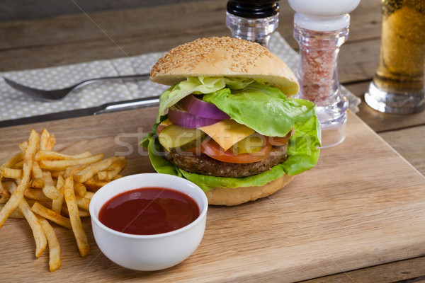 Hamburger, french fries and tomato sauce on chopping board Stock photo © wavebreak_media