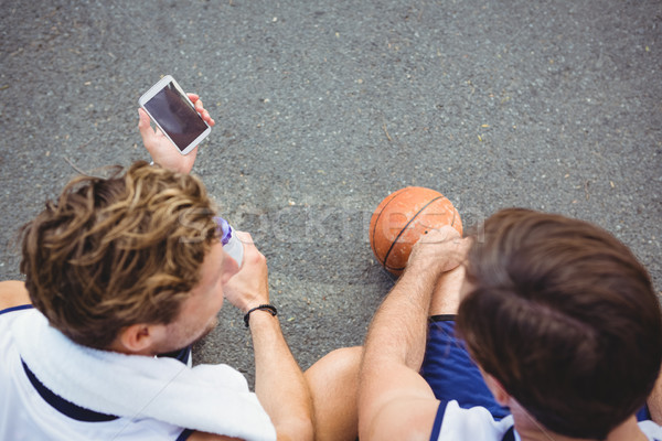 Overhead view of basketball player showing mobile phone to friend Stock photo © wavebreak_media