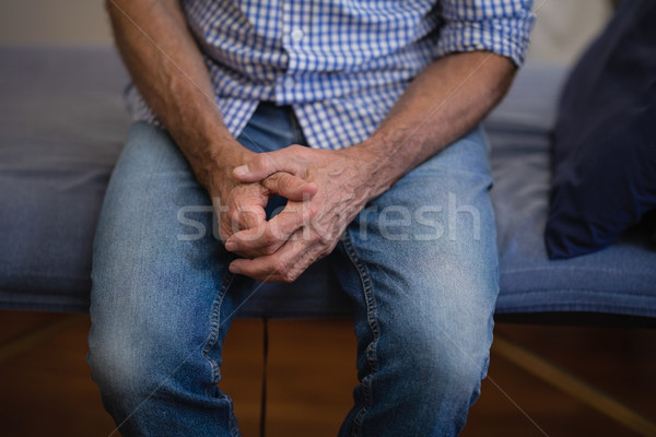 Midsection of senior male patient sitting with hands clasped on bed Stock photo © wavebreak_media