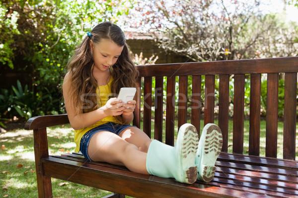 Meisje smartphone vergadering houten bank tuin Stockfoto © wavebreak_media