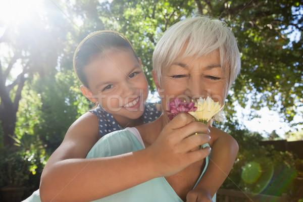 Grandmother smelling flowers while piggybacking granddaughter Stock photo © wavebreak_media