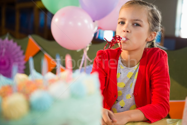 Cute girl blowing party horn during birthday party Stock photo © wavebreak_media