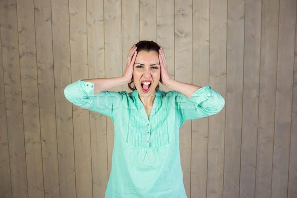 Portrait of woman screaming with head in hands Stock photo © wavebreak_media
