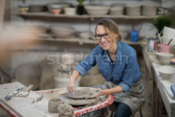 Portrait of female potter molding plate with hand tool Stock photo © wavebreak_media