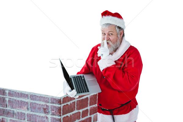 Santa claus with finger on lips while using laptop against white background Stock photo © wavebreak_media