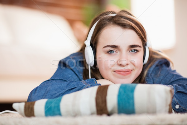 Pretty woman listening music lying on the floor Stock photo © wavebreak_media