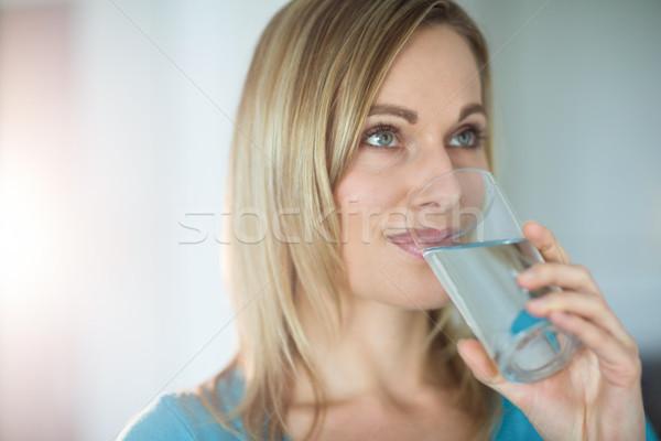 Pretty blonde woman drinking a glass of water Stock photo © wavebreak_media