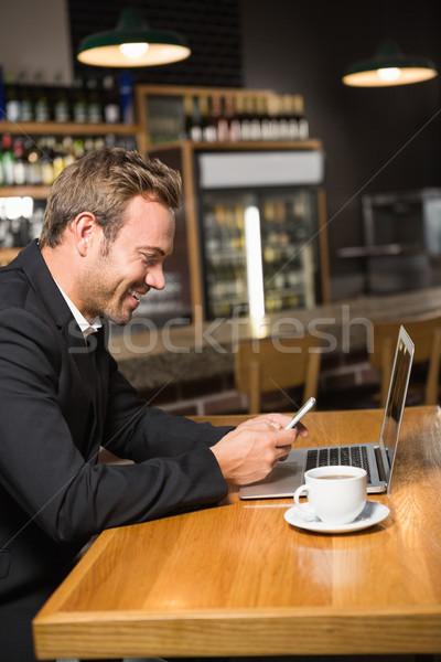 Thoughtful man using laptop and smartphone Stock photo © wavebreak_media