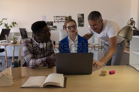 Businessman using virtual reality headset while colleagues discussing over flip chart Stock photo © wavebreak_media