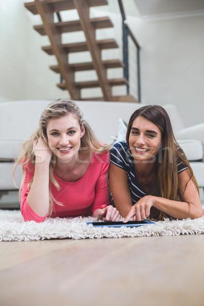 Two beautiful women lying on rug and using digital tablet Stock photo © wavebreak_media