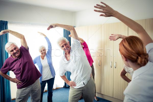 Stock photo: Group of seniors doing exercises with nurse