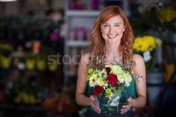 Female florist holding flower vase at flower shop Stock photo © wavebreak_media