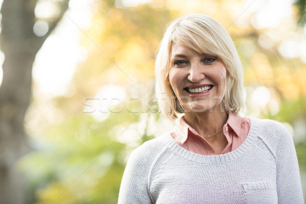 Mature woman smiling while standing in forest Stock photo © wavebreak_media