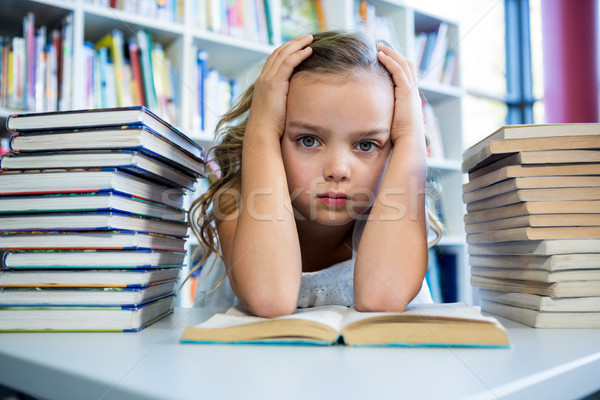 Stock photo: Stressed girl with books at table in school library