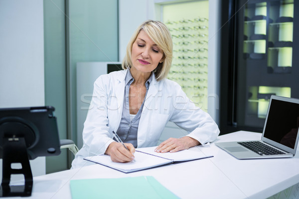 Optometrist writing in book at ophthalmology clinic Stock photo © wavebreak_media